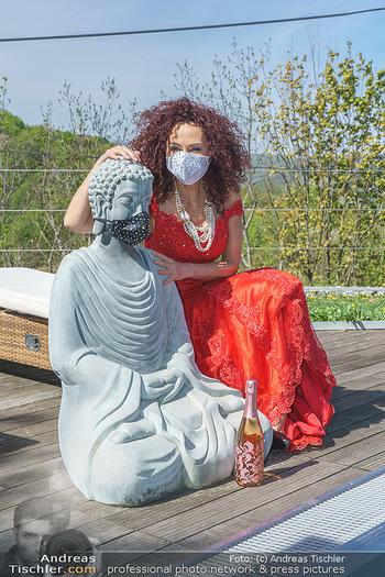 Promis während Corona - Wien - Mi 15.04.2020 - Christina LUGNER mit Cocktailkleid und Buddha Statue mit MNS Mun22