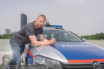 Setbesuch bei SOKO Donau - Filmset Wache am Handelskai, Wien - Di 13.07.2021 - Martin GRUBER (Portrait) mit Polizeiauto vor der Wiener Skyline 2