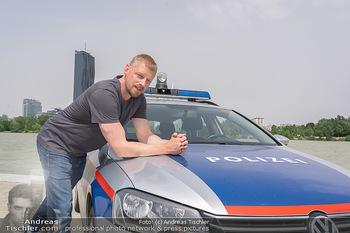Setbesuch bei SOKO Donau - Filmset Wache am Handelskai, Wien - Di 13.07.2021 - Martin GRUBER (Portrait) mit Polizeiauto vor der Wiener Skyline 62