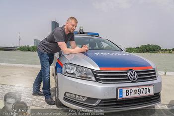Setbesuch bei SOKO Donau - Filmset Wache am Handelskai, Wien - Di 13.07.2021 - Martin GRUBER (Portrait) mit Polizeiauto vor der Wiener Skyline 63